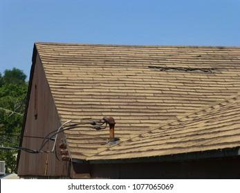 Old damaged brown asphalt composition shingle roof