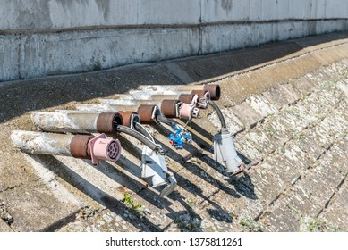 Old damaged electric plug power line installations on the river shore or ocean marine for yachts boats and ships electrification system broken from strong water waves in the storm
