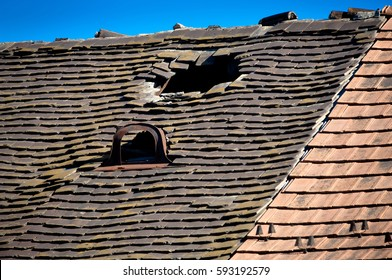 Old damaged tiled roof with broken tiles and a hole on the roof