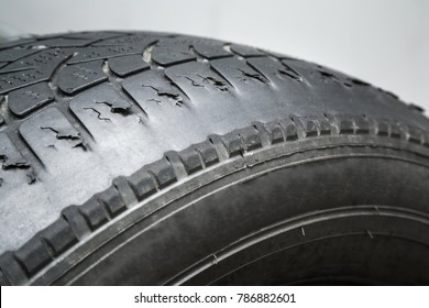 Old, damaged and worn black tire tread. Change time. Tire tread problems and solutions concept.