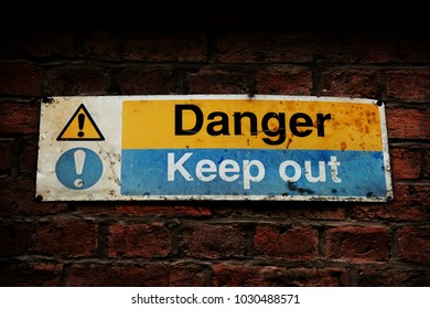 An old Danger Keep out sign on a red brick wall