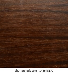 Old dark brown varnished wood with a cracked lacquer fragment as a background
