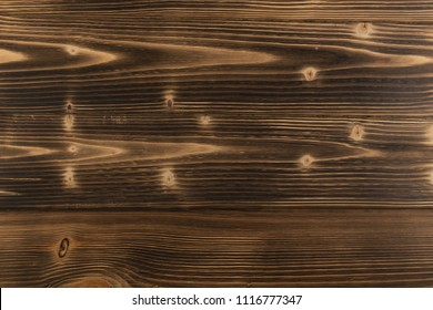 Old dark burnt wood background. Scorched wooden board plank texture. Natural rustic photo backdrop for vintage hipster design
