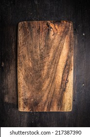 Old dark cutting board on brown wooden table, background