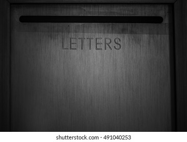old, dark and rustic letter box filling frame with open slit in front.