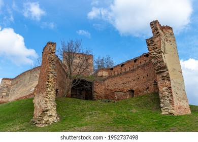 Old, decayed entrance to an medieval fortress with wooden doors and brick walls. Photography of a medieval fortress entrance.