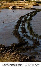 Old decaying flood defences on the Ore Estuary on a sunny day.