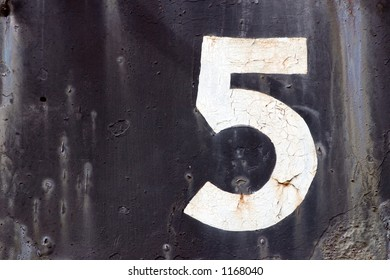 An old decaying train car with the number five painted on the side.