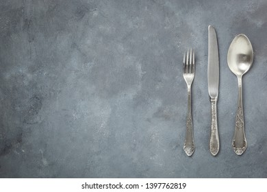 old decorative cutlery on a gray background - space for text