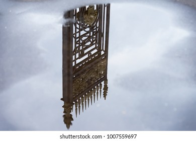 Old decorative iron fence reflected in puddle among the blue sky with clouds after rain. Concept dream, unreality, otherworldly, paradise, nostalgia, romantic mood