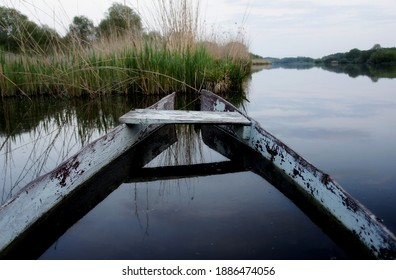 an old decrepit half-sunken boat in the lake in the evening