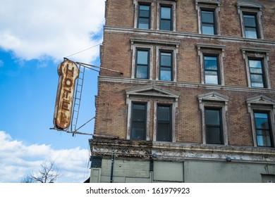 Old, decrepit, weathered sign for a hotel