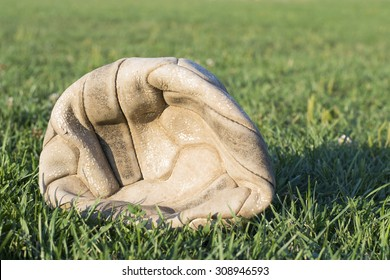 Old deflated soccer ball on the soccer field green grass