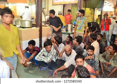 Old Delhi, Delhi - April 8 2013 : Poor people sitting outside a local eatery in Old Delhi waiting for free food about to be distributed