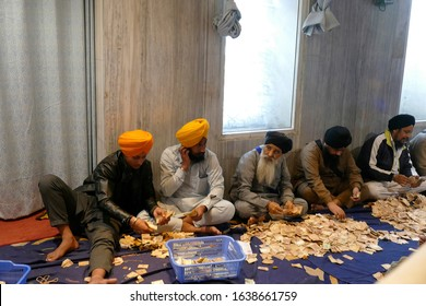 OLD DELHI - DEC 18, 2019 - Men and women sort donations to the Gurudwara Sis Ganj Sahib ji Sikh temple, Old Delhi, India