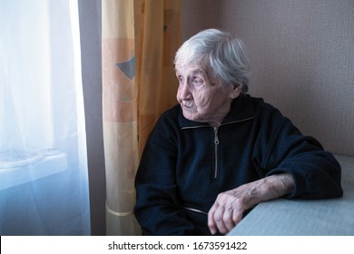 An old depressed loneliness woman in his house looking at nothing.