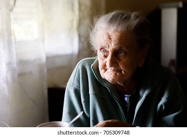 Old depressed woman. An elderly lonely woman sits at a table in the kitchen near the window and drinking tea.