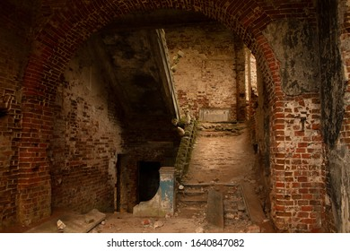 Old derelict building room interior, arched doorway and staircase