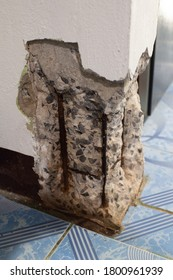 Old destroyed concrete pillar with rusty iron fittings