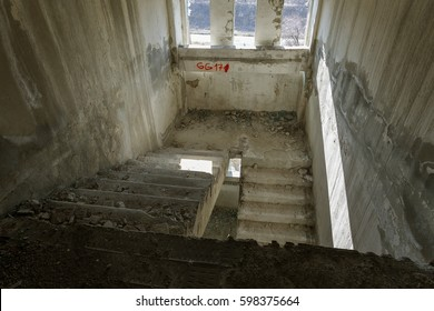 Old destroyed concrete, stone staircase in interior of ruins of unfinished administrative building of business center. Ruined old staircase in interior of abandoned factory building. Trash interiors