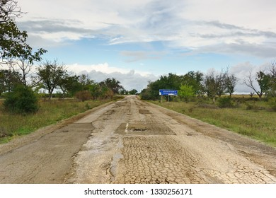 """Old destroyed road in Crimea. Road sign with the names of villages in Russian """"Abrikosovka And Pervomayskoe"""". Kirovsky district, Republic of Crimea, Russia"""