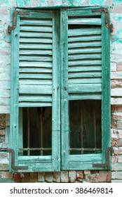 Old destroyed window with green shutters