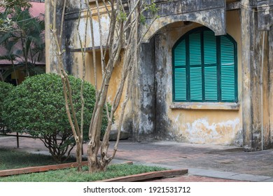 Old and deteriorated yellow building with green windows in Hanoi, Vietnam