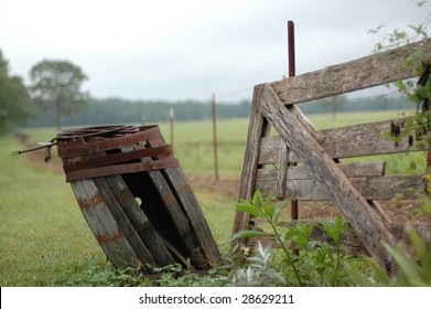 An old deteriorating wooden barrel leans away from a fence in the country.