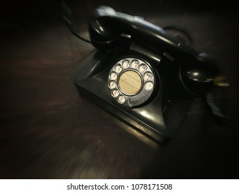 The old dial telephone focused on the dial number pad with motion blurred effect around the phone - concept, flashback to the old day