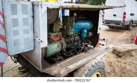 Old diesel generator with oil stains. Vintage engine. Trailer with the old diesel compressor. Mobile compressor parked at building site. Diesel.