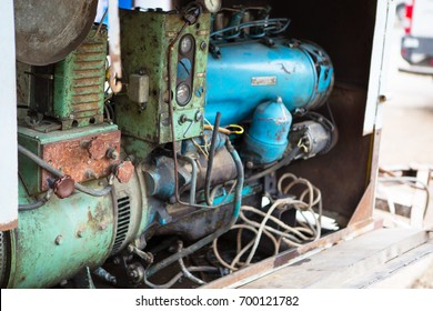 Old diesel generator with oil stains. Vintage engine. Trailer with the old diesel compressor. Mobile compressor parked at building site. Diesel.