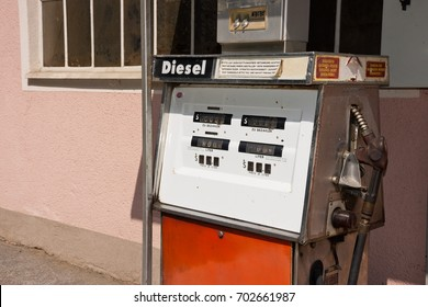 Old diesel petrol pump in Austria. Filling station in front of a pink colored house. Translation of warnings in German for safe refueling: stop engine, no open fire, no smoking, no spillage.