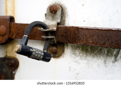 An old digital dial-padded combination padlock keeps the deadbolt on the doors of an old rusted semi trailer from unauthorized access to the goods stored inside.