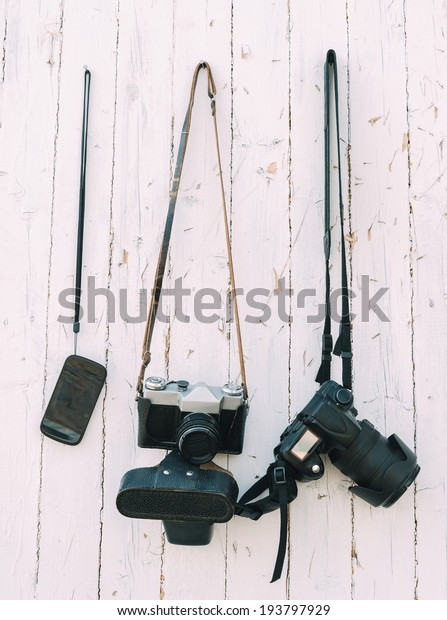 Old and digital photo cameras are hanging on the wooden wall