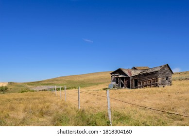 old dilapidated abandoned  farm house on a prairie landscape with a barbed wire fence in the foreground