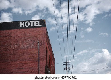 old dilapidated brick motel with cloudy sky