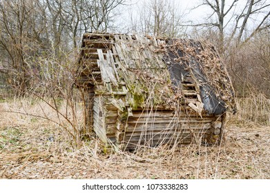 Old old dilapidated little wooden abandoned ruined rickety broken village house of beams, logs and sticks in the wilderness, in the woods