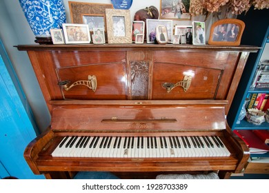 Old dilapidated piano with portraits and pictures on the lid . Salzburg, Austria - October 15, 2019