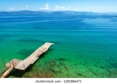 Old dilapidated pier extending towards the Ionian Sea in Corfu, Greece