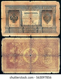 Old dilapidated Russian banknote of 1 ruble in 1898. Isolated on a black background. The front and back side.