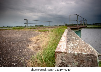 Old and dilapidated vintage rampart along the waterfront in a river landaschap of the Netherlands. Concrete mooring jetty in abandoned state.