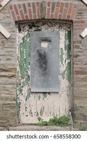 An old dilapidated white and green door in Liskeard, Cornwall