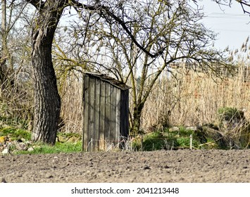 Old, dilapidated wooden toilet in the countryside.