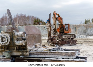 old dirty bandsaw and other machines for processing stone blocks stands in a quarry for the extraction of marble