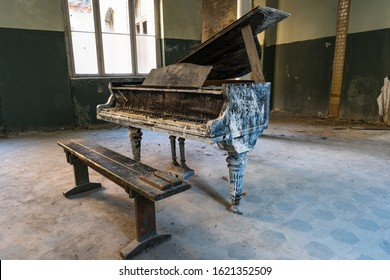 Old dirty black piano with a brown bench in an empty abandoned room - large windows and green walls