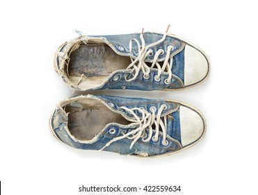Old and dirty blue canvas sneakers isolated on white background