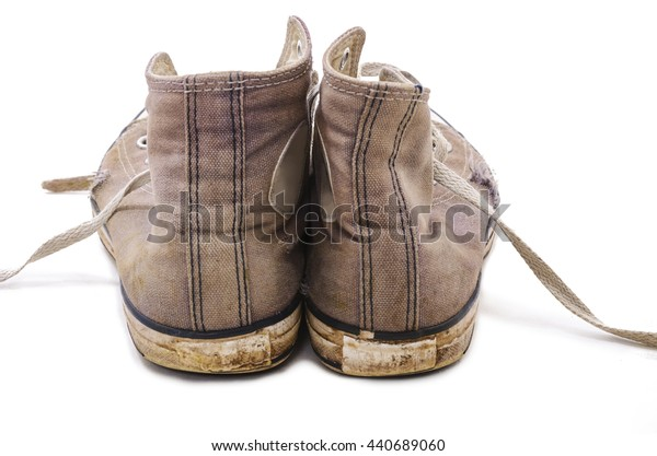 Old and dirty blue canvas sneakers. Isolated on white background