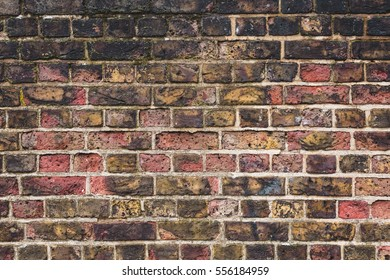 Old Dirty Brick Wall with Black, Red, and Pink Bricks as Textured Background in London, England