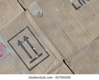 old dirty brown cardboard wrinkled, torn stickers black letters and arrows of the box