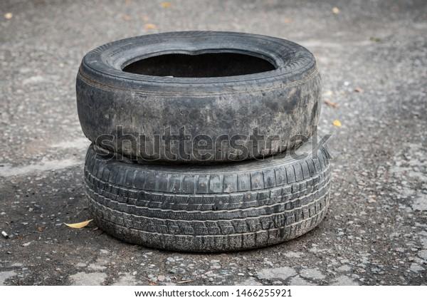 Old dirty car tires on cracked asphalt. Close-up